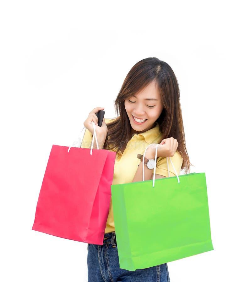 Appy asiatisk flickahåll som shoppar den pappers- påsen och mobilen på vit isolator royaltyfri foto