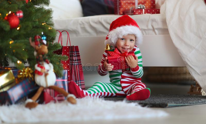 Appy baby boy in pajamas with gifts on christmas morning near royalty free stock photo