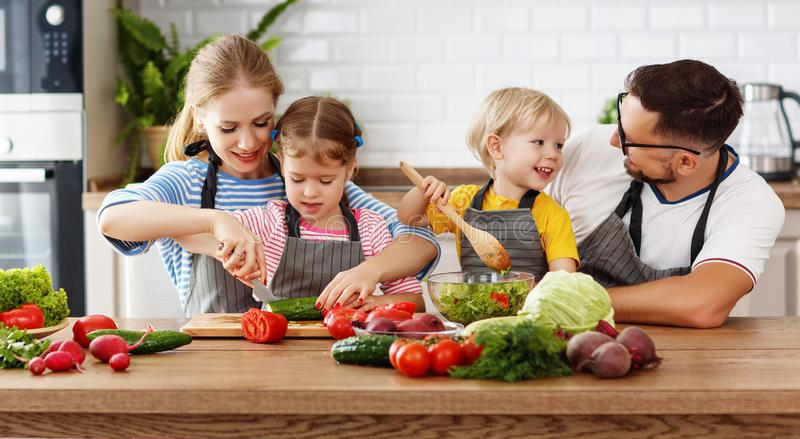 Appy family with child preparing vegetable salad stock photos