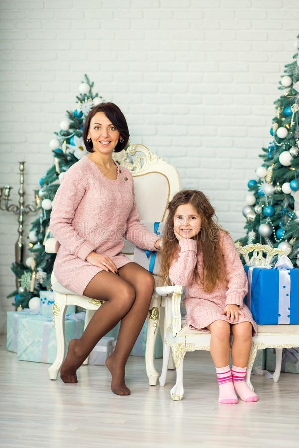 Appy family mother and child daughter on Christmas morning at the Christmas tree with gifts stock image