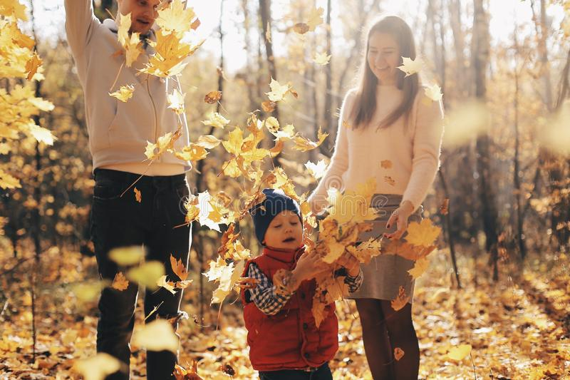 Appy family with son in autumn park throws yellow leaves. royalty free stock photo