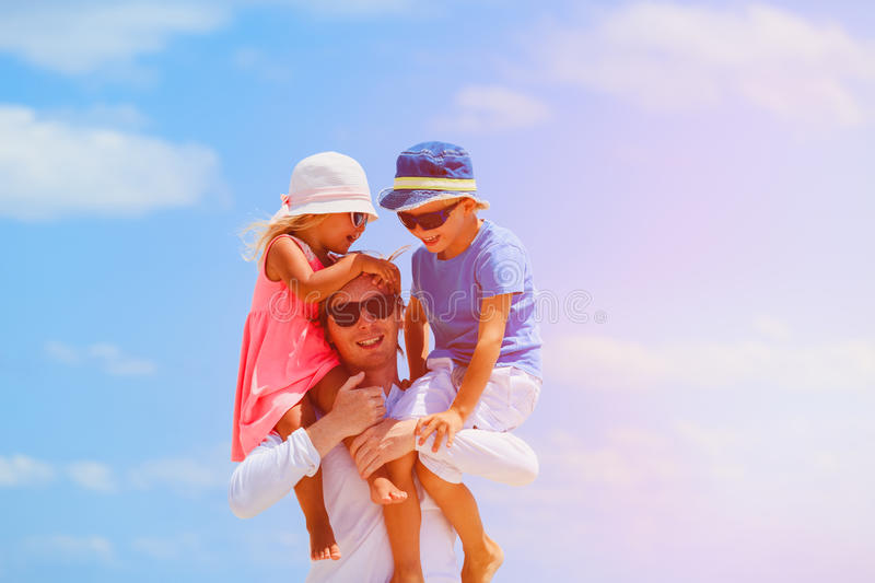 Appy father with two kids on shoulders at sky stock photography