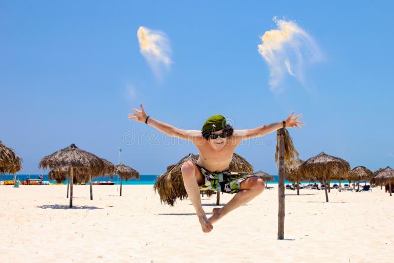 Appy młody człowiek skacze dla radości na plaży, przeciw niebieskiemu niebu i oceanowi zdjęcie royalty free