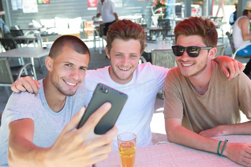 Appy mannelijke vrienden selfie en het drinken bier die bij bar nemen stock afbeelding