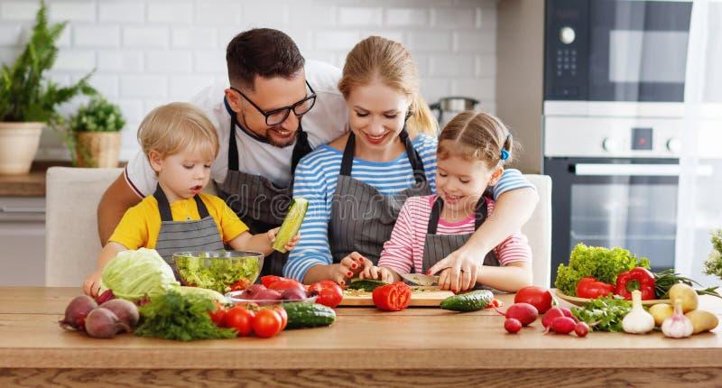 Appyfamilie met kind die plantaardige salade voorbereiden stock fotografie