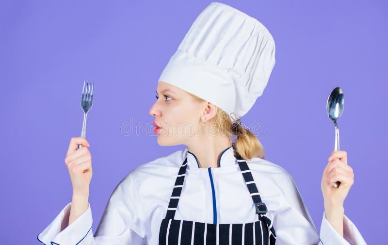 Après étiquette d'ustensiles de consommation Jolie femme tenant des ustensiles d'acier inoxydable Cuisinier sexy avec des batteri photo stock