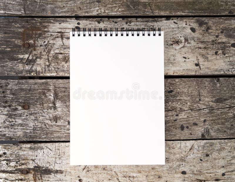 apra il blocco note con la pagina bianca pulita sulla vecchia tavola di legno rustica invecchiata, vista superiore immagine stock libera da diritti