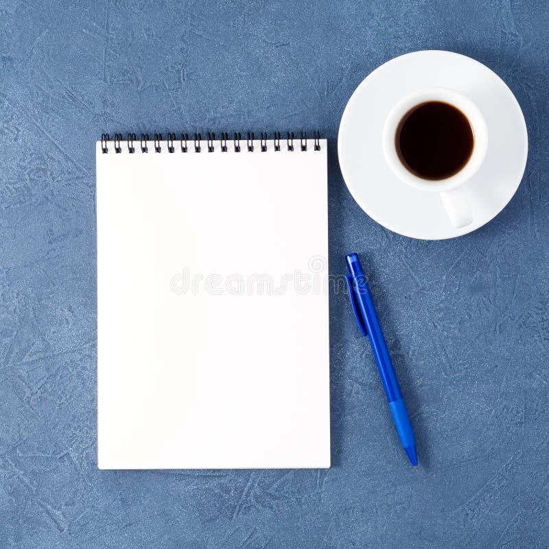 apra il blocco note con la tazza pulita della pagina bianca, della penna e di caffè sulla tavola di pietra blu scuro invecchiata, fotografia stock libera da diritti