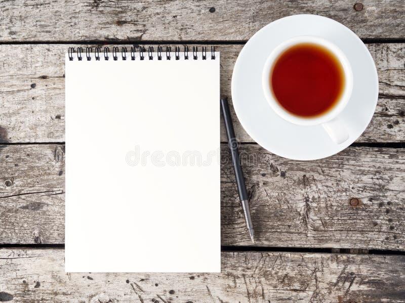 apra il blocco note con la tazza pulita della pagina bianca, della penna e di caffè sulla vecchia tavola di legno rustica invecch fotografie stock libere da diritti