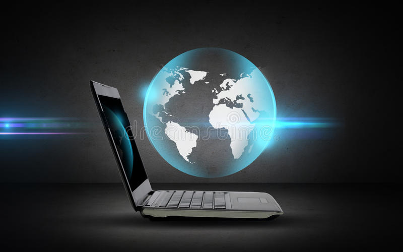 Apra il computer portatile con la proiezione del globo fotografia stock libera da diritti