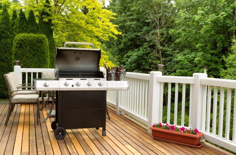 Apra il fornello del BBQ e la birra in bottiglia sul patio all'aperto del cedro fotografia stock