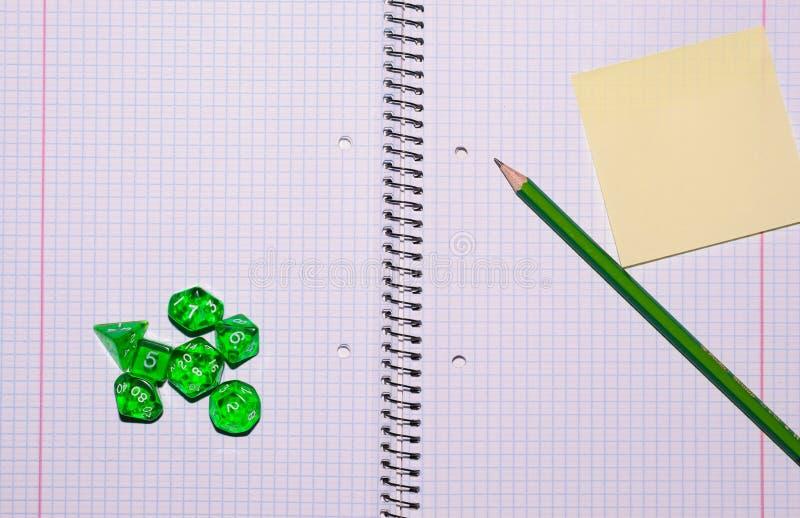 Apra il quaderno con la carta, la matita appiccicosa ed il gioco di ruolo dic immagini stock libere da diritti