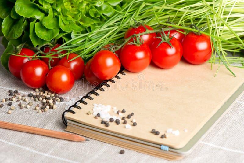 Apra il taccuino con i pomodori, la erba cipollina, spezie immagini stock
