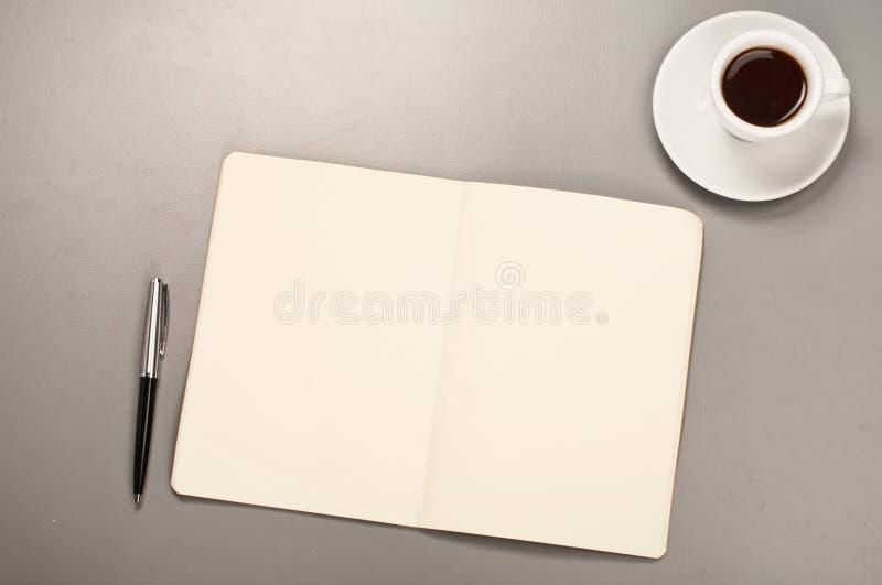 Apra il taccuino con le pagine in bianco con una tazza di caffè e della penna fotografia stock