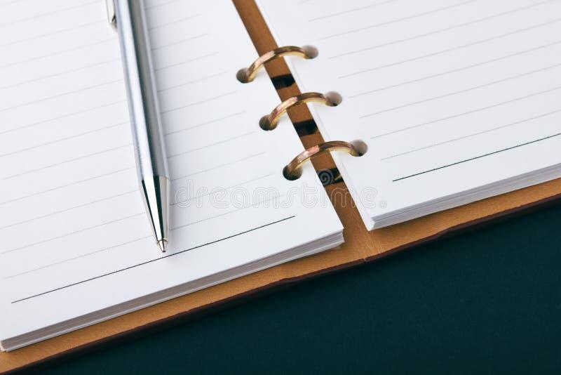 Apra il taccuino e la penna d'argento immagine stock