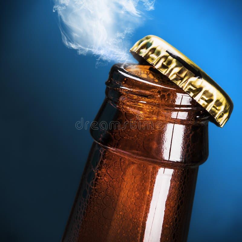 Apra la bottiglia della birra su un blu immagini stock libere da diritti