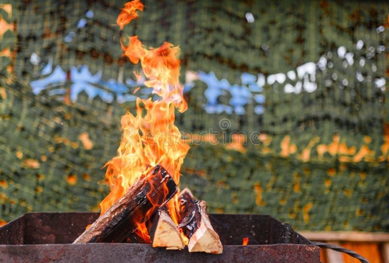 Apra la combustione del fuoco in un barbecue all'aperto fotografia stock