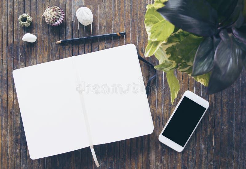 Apra la foto di disposizione del piano del taccuino Blocco note con la pagina in bianco e lo smartphone fotografia stock