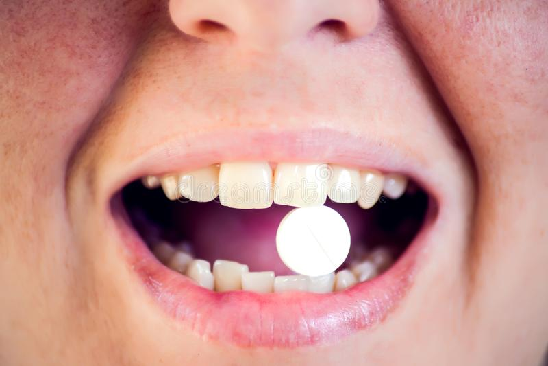 Apra la pillola della medicina della tenuta della bocca sulla lingua Donna che cattura medicina Concetto della medicina e di sani fotografia stock