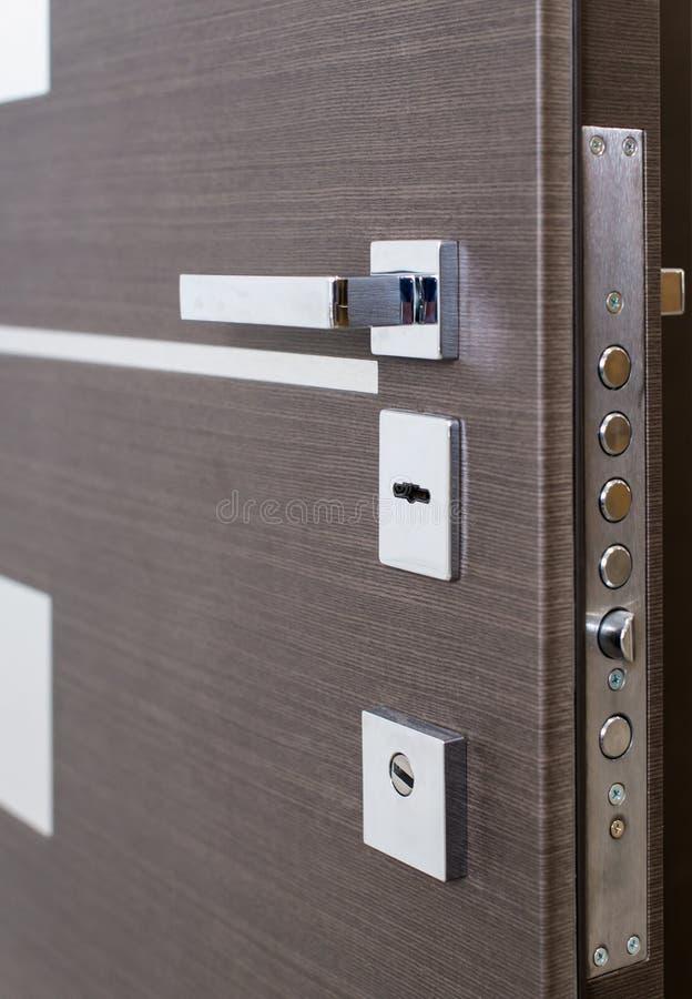 Apra la porta corazzata Serratura di porta, primo piano della porta di marrone scuro Interior design moderno, maniglia di porta C immagine stock libera da diritti
