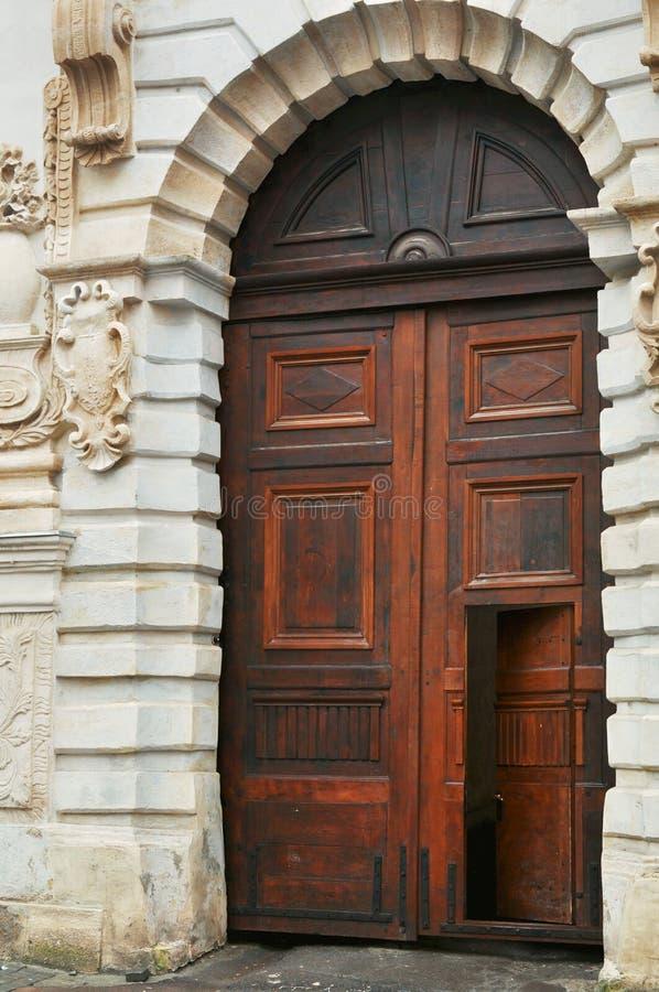 Apra la porta di legno del vecchio broun medievale di stile sulla costruzione classica della facciata a Leopoli Ucraina fotografia stock libera da diritti