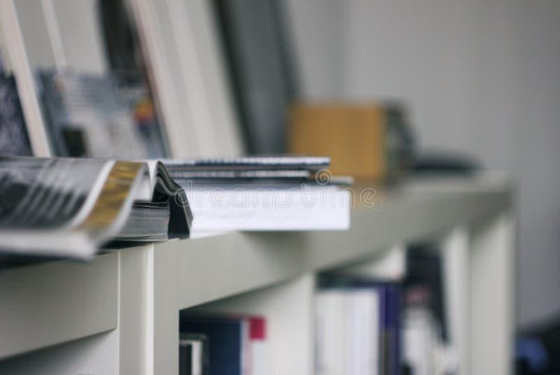 Apra la rivista sullo scaffale bianco, gli scaffali per libri, l'ufficio moderno, fuoco selettivo fotografia stock libera da diritti