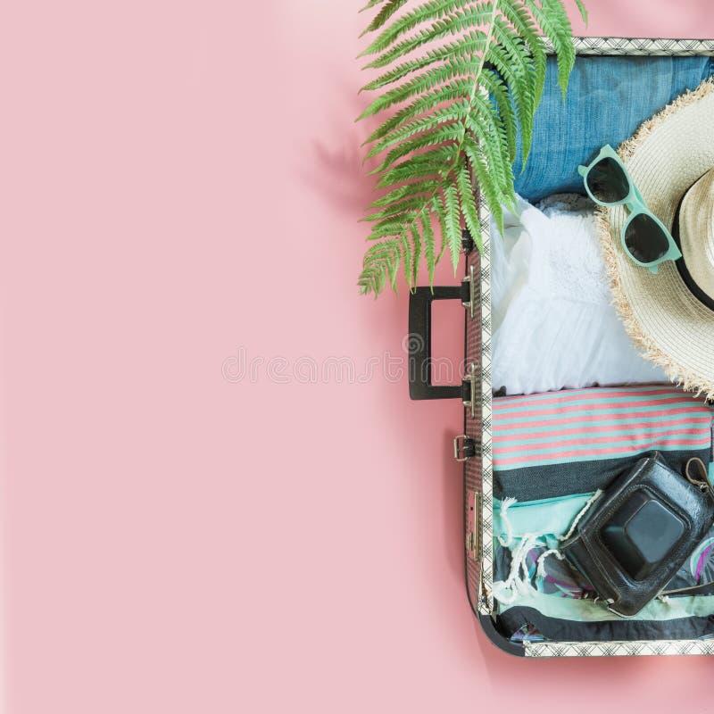 Apra la valigia con i vestiti femminili per il viaggio sul rosa pastello Vista superiore con lo spazio della copia Viaggio di con immagini stock libere da diritti