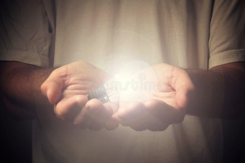Apra le mani con la lampadina fotografie stock