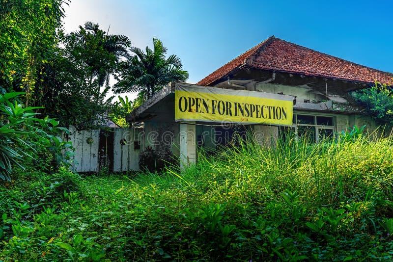 Apra per l'insegna di plastica del segno di ispezione davanti alla costruzione abbandonata danno vuoto della Camera con il giardi immagine stock libera da diritti