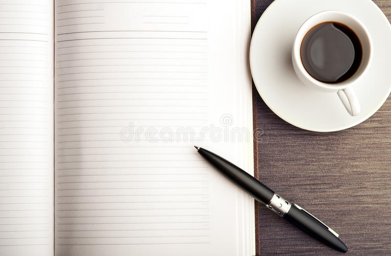 Apra un taccuino, una penna e un caffè bianchi in bianco sullo scrittorio immagine stock