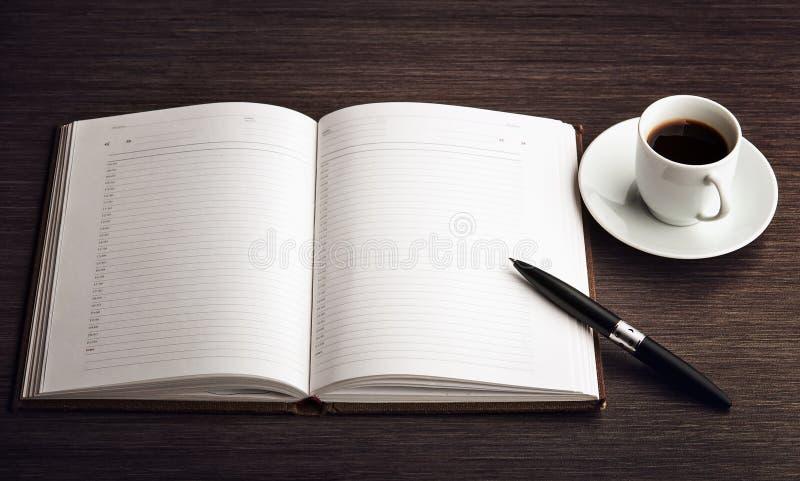 Apra un taccuino, una penna e un caffè bianchi in bianco sullo scrittorio fotografia stock libera da diritti