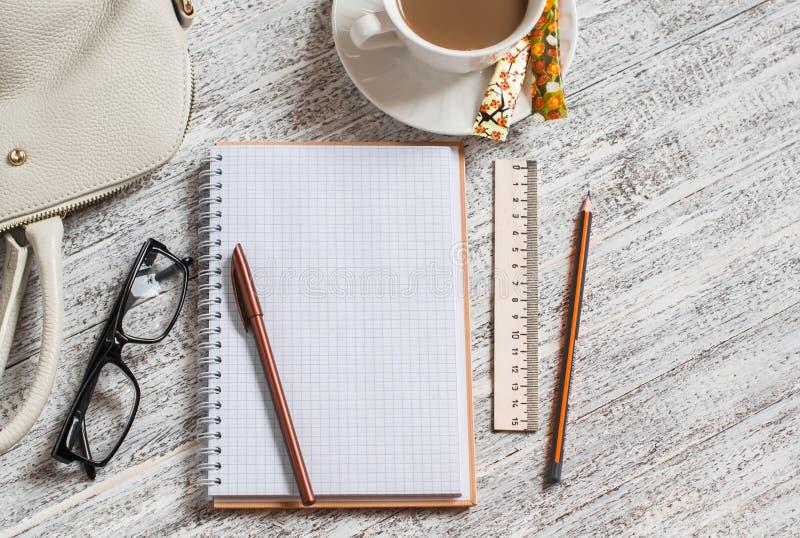 Apra un taccuino, una penna, una borsa delle donne, un righello, una matita e una tazza di caffè bianchi in bianco fotografia stock