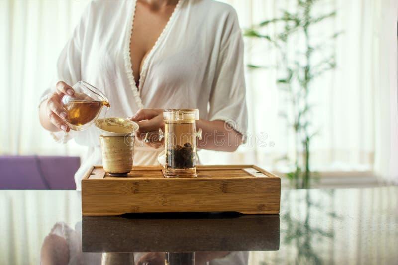 Apreciando a cerimônia de chá Retrato da vista lateral da mulher bonita nova no copo da terra arrendada do quimono do chá que olh fotografia de stock royalty free