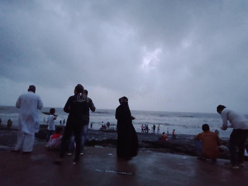 Apreciando a chuva na praia do seasidec imagens de stock