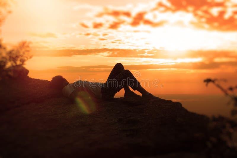 Apreciando e relaxando o por do sol, mulher que encontra-se na rocha e que aprecia na vista imagem de stock royalty free