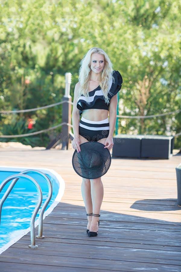 Apreciando o bronzeado e as férias Retrato colorido da jovem mulher bonita no levantamento de encontro do roupa de banho preto re fotos de stock