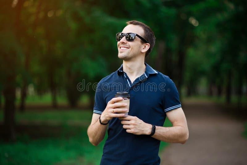 Apreciando o caf? fresco Homem novo consider?vel no vestu?rio desportivo que guarda o copo descart?vel e que sorri ao andar atrav foto de stock royalty free