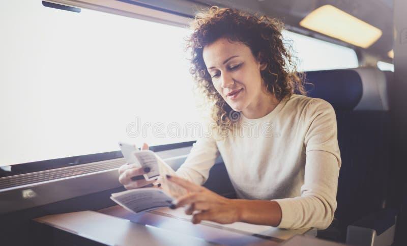 Apreciando o conceito da viagem de negócios Menina moreno bonita nova do turista que viaja no trem que senta-se perto da janela foto de stock