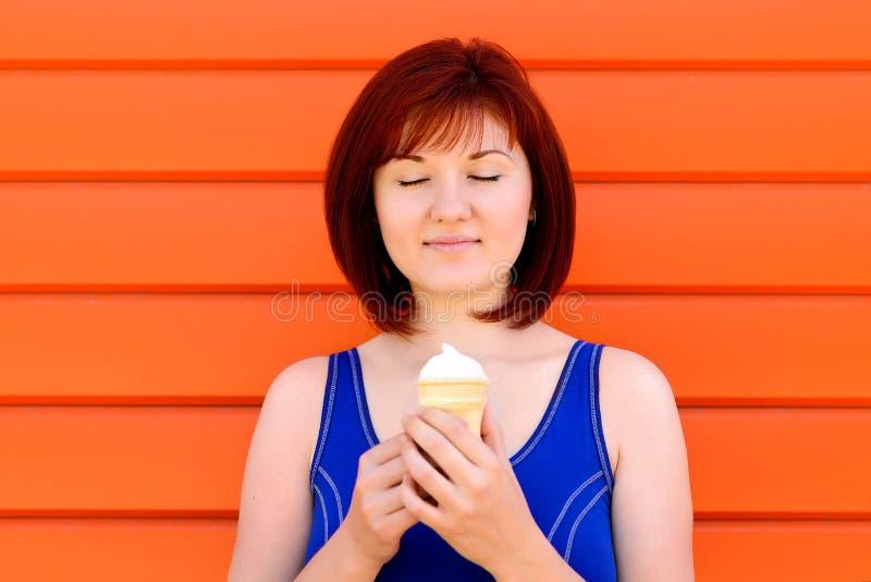 Apreciando o momento: jovem mulher na posição azul da camisa com olhos próximos que sorri e que realiza nas mãos um gelado imagem de stock royalty free