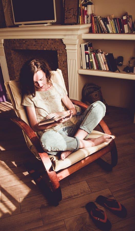 Apreciando o tempo em casa Mulher que relaxa na cadeira moderna confortável que lê o livro de papel Luz natural HOME acolhedor Ap fotos de stock