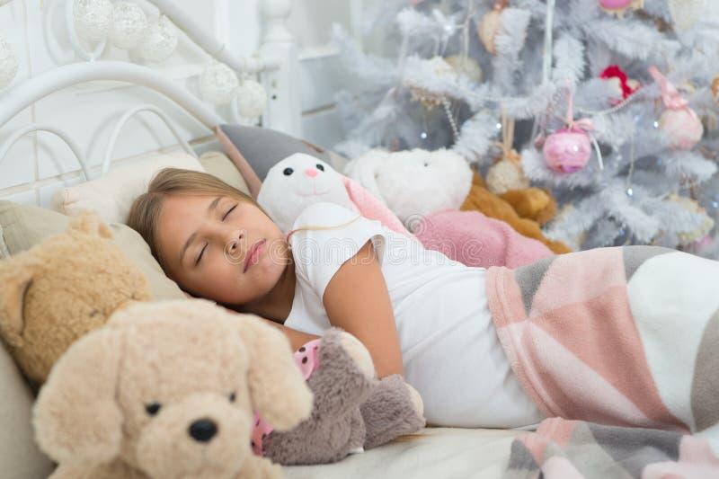 Apreciando o xmas em casa Pouco sono da criança na árvore de Natal Menina que encontra-se na cama com brinquedos A menina bonito  imagens de stock