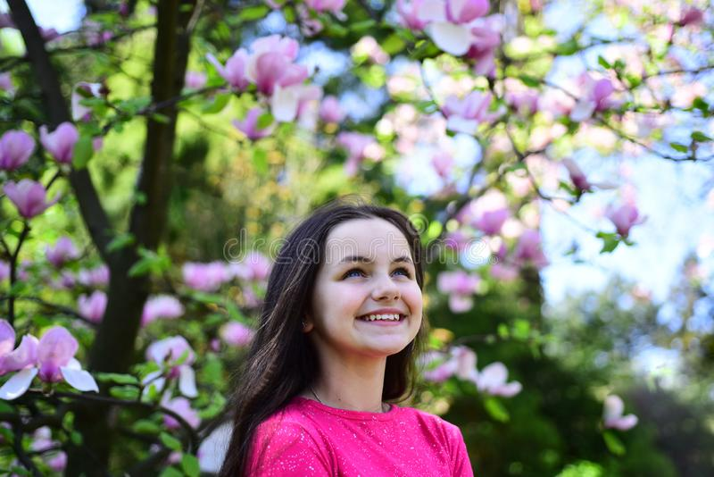 Apreciando a primavera A menina bonita perto da árvore de florescência aprecia a flor da magnólia Sorriso feliz da menina bonito  fotos de stock