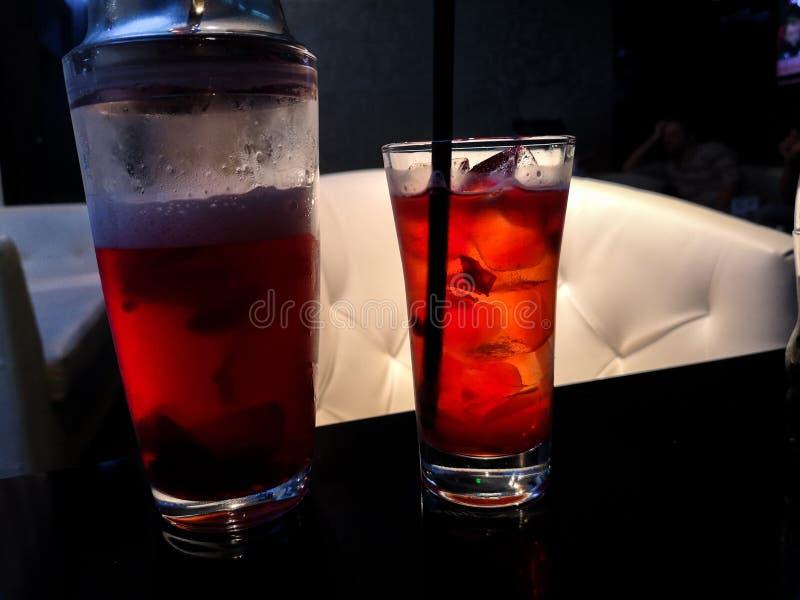 Apreciando um chá de gelo frio delicioso da framboesa vermelha em um café imagem de stock