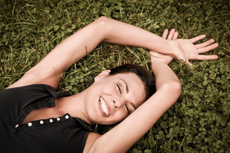 Apreciando a vida - mulher que encontra-se na grama foto de stock