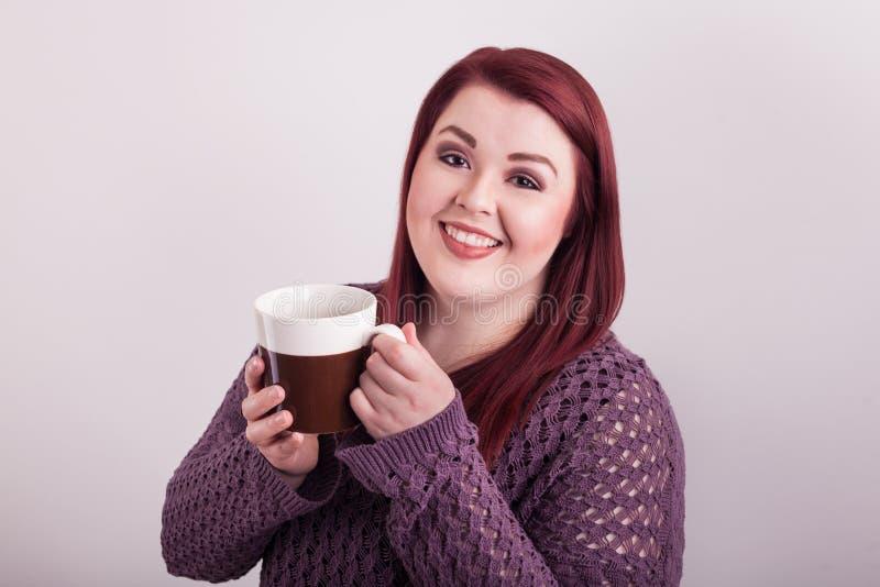 Apreciar um vermelho novo da xícara de café dirigiu o sorriso agradável fêmea imagens de stock royalty free