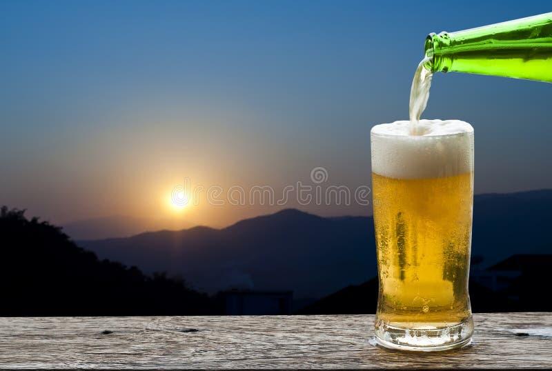 Aprecie a cerveja com por do sol fotografia de stock royalty free