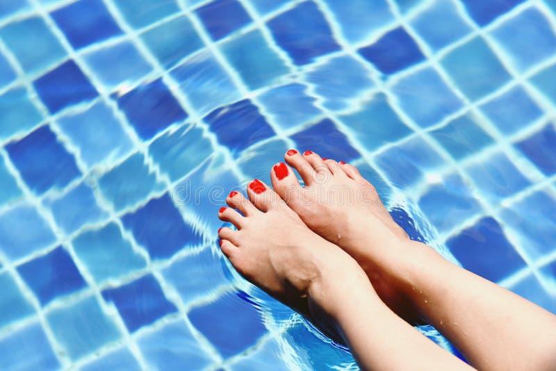 Aprecie a menina bonita que relaxa na piscina, pés da mulher na água foto de stock