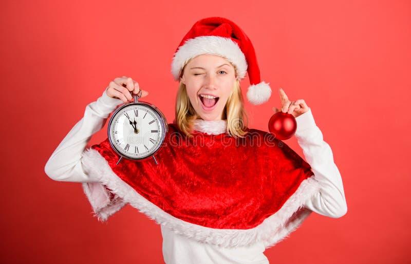 Aprecie o ano novo feliz da celebração O traje feliz de Santa do desgaste da menina comemora o fundo vermelho da decoração da bol fotografia de stock royalty free