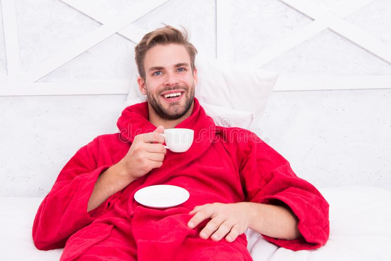 Aprecie o caf? da manh? Manh? feliz Café considerável da manhã da bebida do homem homem farpado feliz na cama Bom modo gourmet imagem de stock royalty free