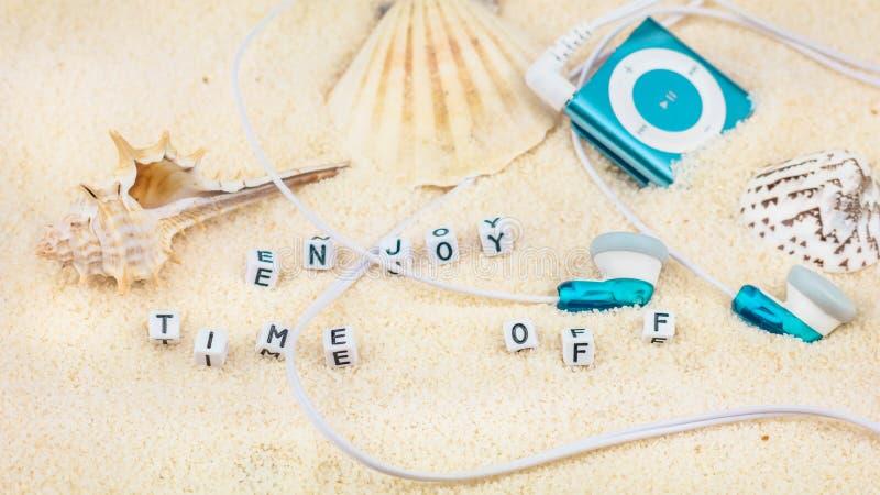Aprecie o tempo fora das letras entre shell do mar e o jogador audio no Sandy Beach fotografia de stock